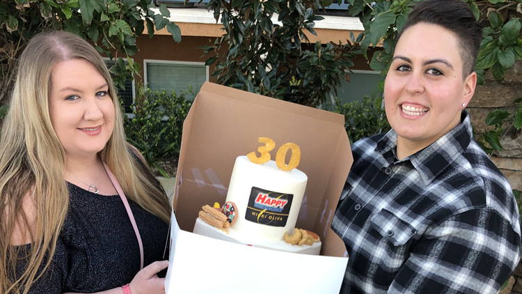 Samantha and Nikki pose with the cake