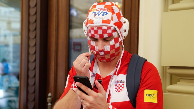 Croatia's supporter puts on face paint in the colors of Croatia in Moscow on July 11, 2018 ahead of the the semi-final match England v Croatia during the Russia 2018 World Cup football tournament.