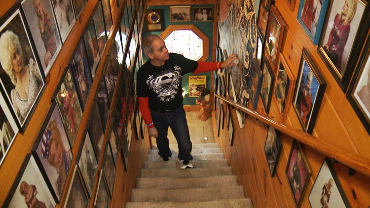 Harrell Gabehart browses the stairwell walls covered with photos of Dolly Parton.