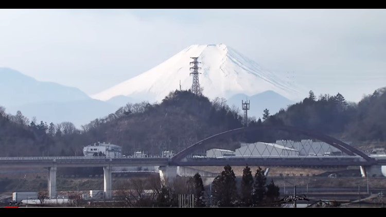 Japan's SC maglev line is seen in the foothills of Mt. Fuji. The train's low profile is barely visible moving across a viaduct bridge.