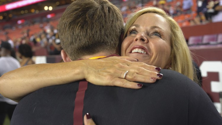 Sherry Gruden hugs son, Jack, on football field