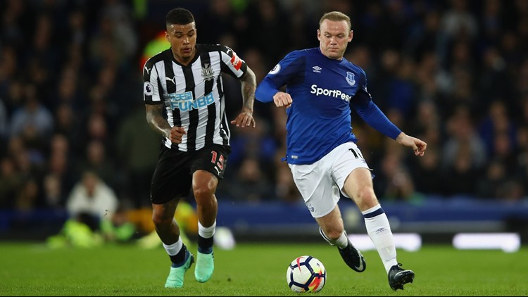 LIVERPOOL, ENGLAND - APRIL 23: Wayne Rooney of Everton and Kenedy of Newcastle United battle for possession during the Premier League match between Everton and Newcastle United at Goodison Park. (Photo by Clive Brunskill/Getty Images)