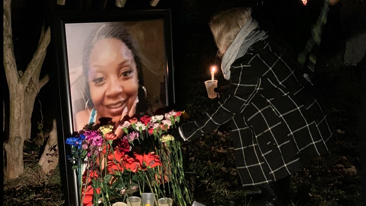 A mourner places a rose in front of a portrait of Anita Ellis. The New Carrollton woman's home caught fire Jan. 18, a fire that proved fatal.