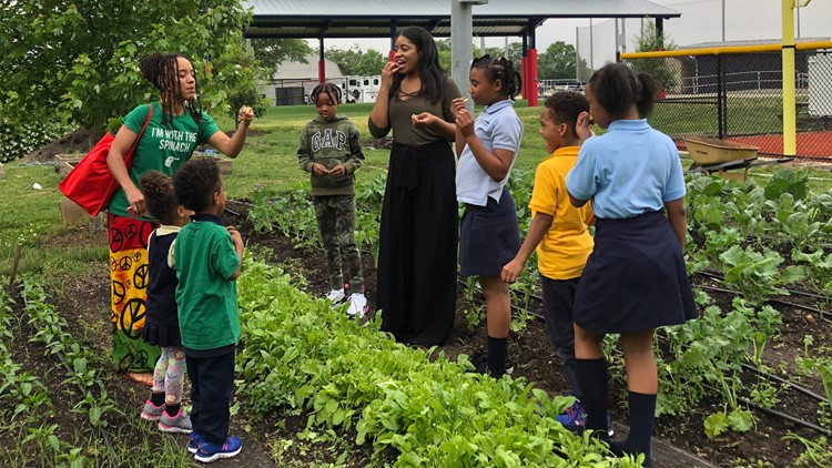 Maya Walker, in the long black skirt, gives an impromptu tour of the Nationals Youth Baseball Academy garden