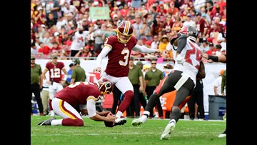 Redskins kicker shows off talents while holding baby