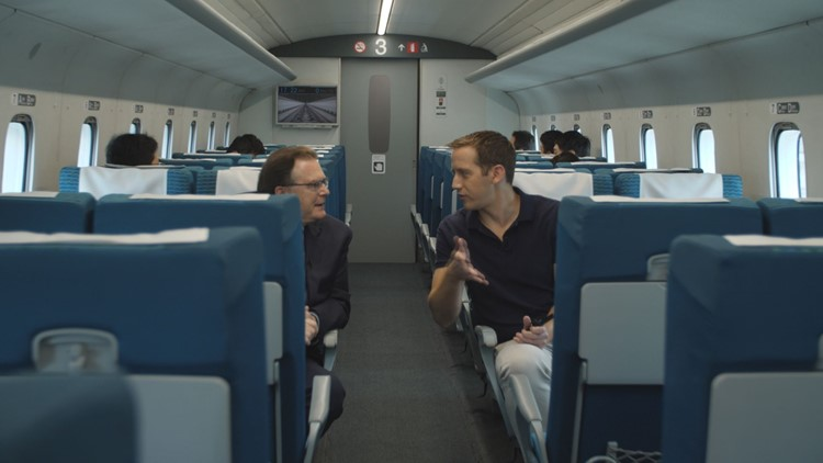 WUSA9 reporter Mike Valerio (right) speaks with BWRR chairman & CEO Wayne Rogers (left) aboard Japan's SCMaglev, June 10, 2019.