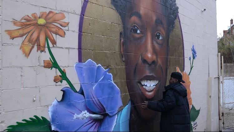 Monique Scott embraces mural of her son, Maurice.